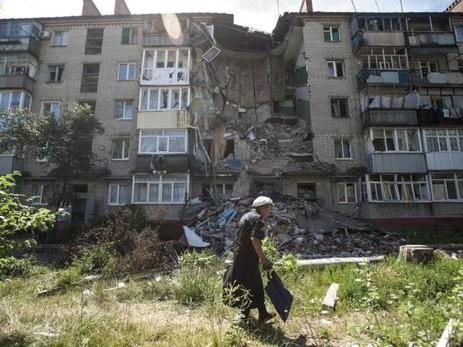 Eine Frau geht an einem zerstörten Haus in Slawjansk vorbei Quelle Keystone
