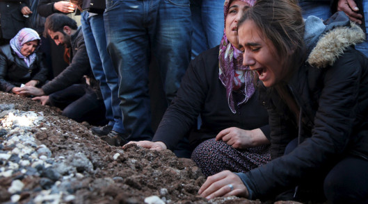 Relatives of Siyar Salman mourn over his grave during a funeral ceremony in the Kurdish dominated southeastern city of Diyarbakir, Turkey, December 15, 2015. According to local media, Salman, a 19-year old man, was killed on Monday in Diyarbakir during a protest against the curfew in Sur district. REUTERS/Sertac Kayar - RTX1YSUN